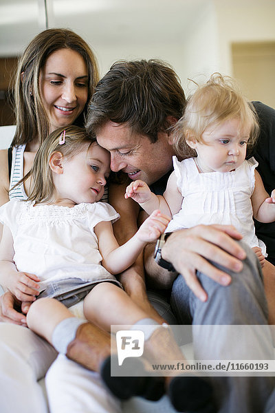 Mid adult couple with baby and toddler daughters on lap
