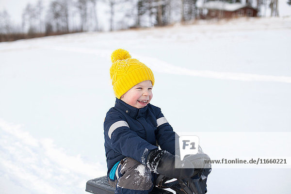 Young boy sitting on sledge  in snow covered landscape