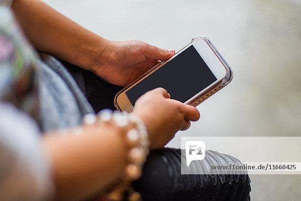Ausschnitt eines Mädchens mit Smartphone