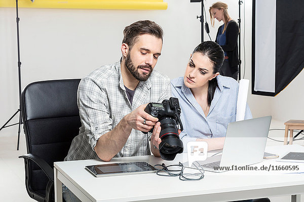 Stylist and photographer reviewing shoot on digital SLR in photography studio