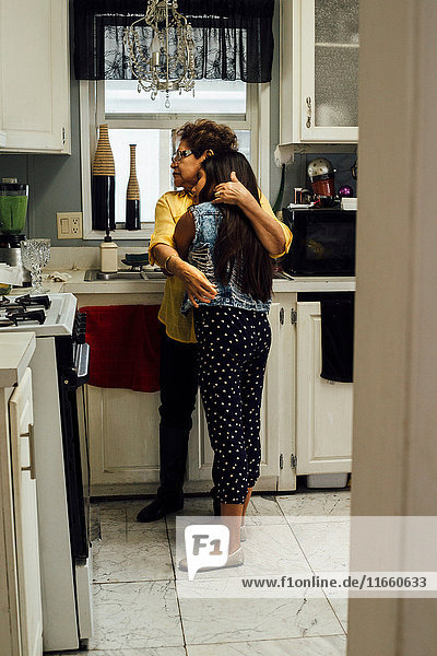 Großmutter umarmt Enkelin in der Küche