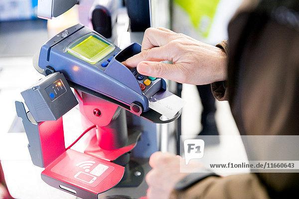 Ältere Frau benutzt Kreditkartenautomat zum Bezahlen von Einkäufen  Nahaufnahme