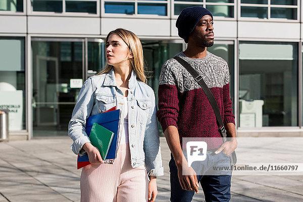 Junger Mann und Frau im Freien  Frau mit Notizbüchern und Akten.