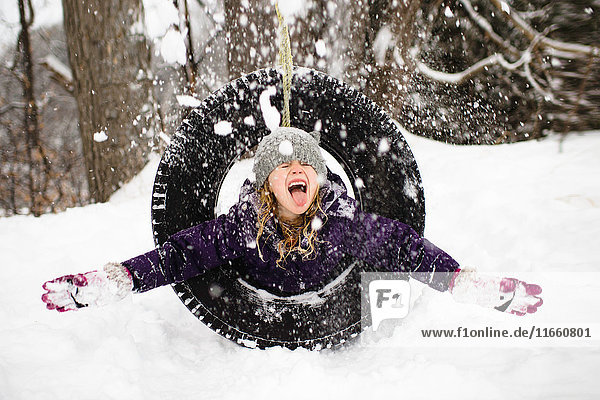 Girl playing in snow on tire swing
