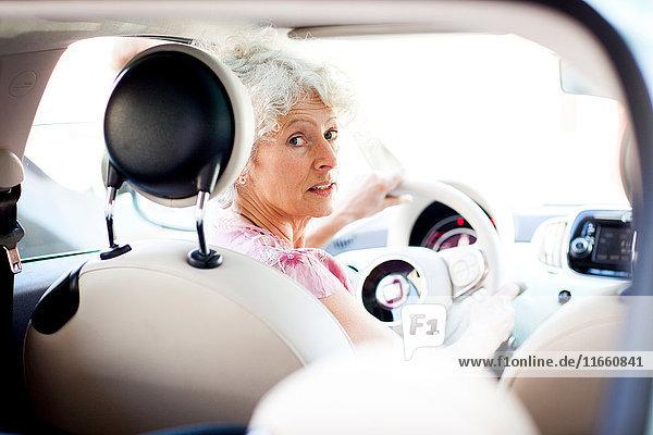 Porträt einer reifen Frau  die im Auto über ihre Schulter schaut