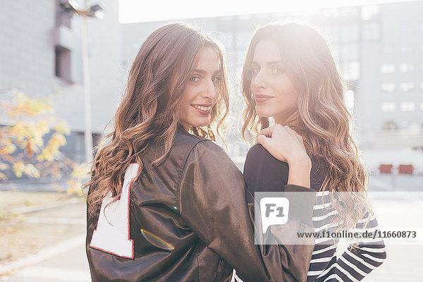 Porträt von Zwillingsschwestern  im Freien  über die Schulter schauend