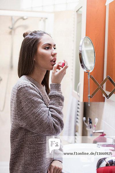 Young woman  looking in bathroom mirror  applying lipstick
