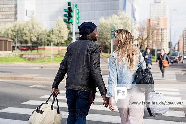 Junges Paar  das die Straße überquert  mit Gepäckträgern  Rückansicht  lächelnd