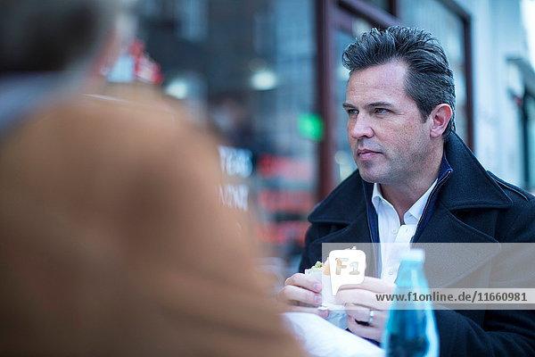 Geschäftsleute im Straßencafé beim Mittagessen