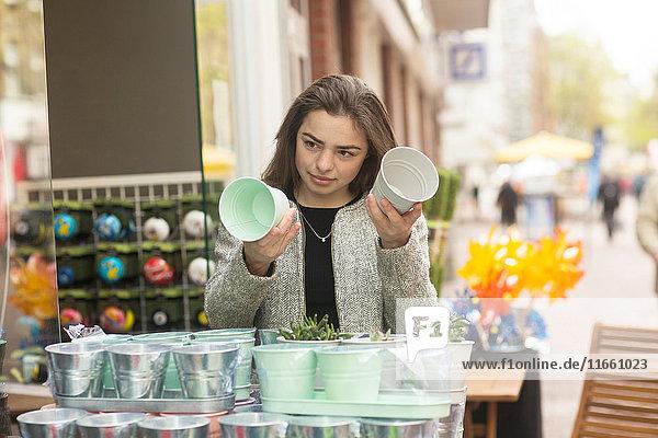 Junge Frau vergleicht Blumentöpfe am Marktstand
