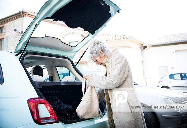 Reife Frau mit Einkaufstasche schaut in den Kofferraum