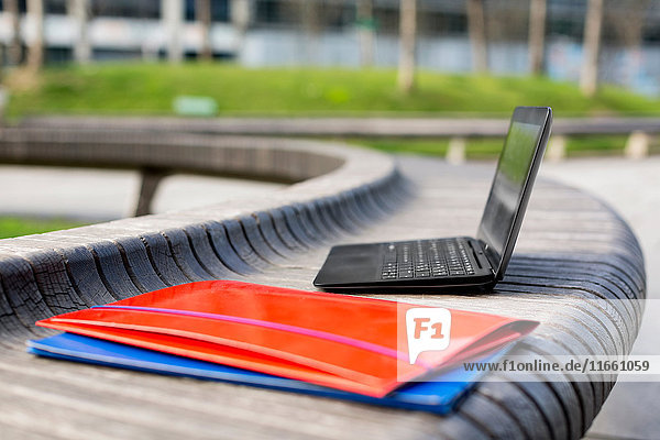 Open laptop and paperwork files on bench  outdoors