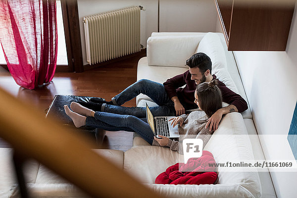 Young couple relaxing on sofa  looking at laptop  elevated view