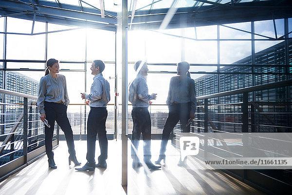 Geschäftsmann und -frau unterhalten sich auf dem Balkon des Büros