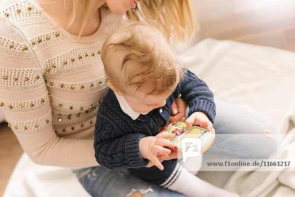 Mother holding baby with toy smartphone