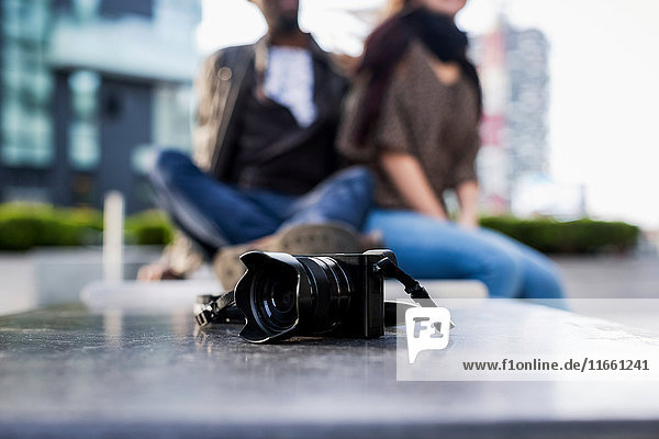 Camera in front of young couple on city wall