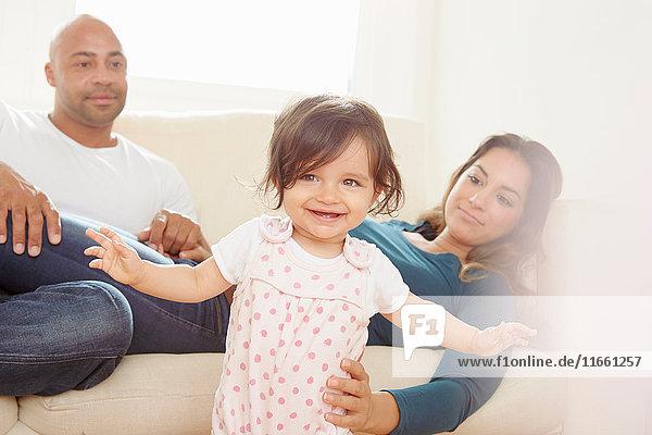 Mutter auf dem Sofa  die ihrer Tochter beim Wackeln die Hand reicht