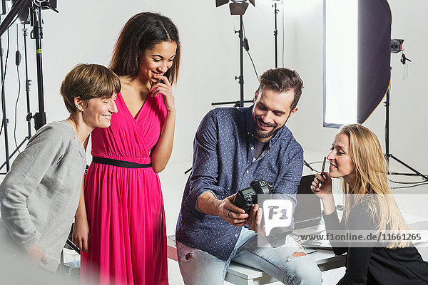 Photographer  stylists and model reviewing photo shoot on digital SLR in photography studio