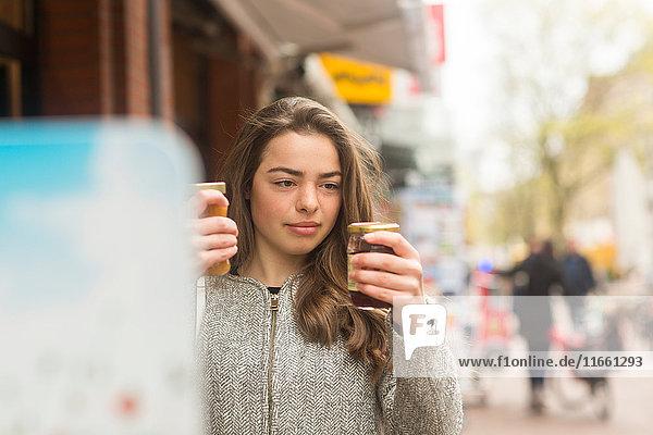 Junge Frau vergleicht Einmachgläser am Marktstand