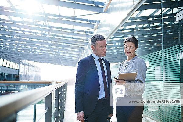 Geschäftsfrau und Mann lesen Papierkram auf Bürobalkon