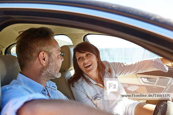 Couple in car  man driving  woman pointing ahead  laughing