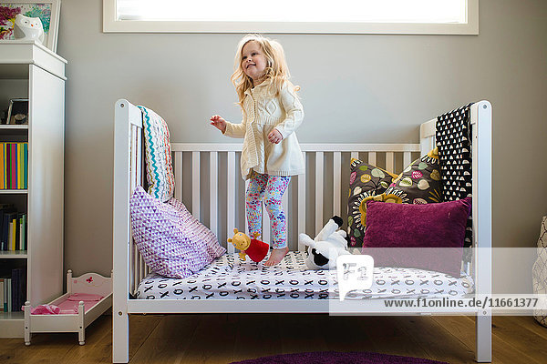 Girl jumping on day bed