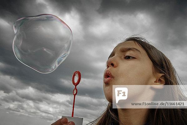 Mädchen bläst große Seifenblase
