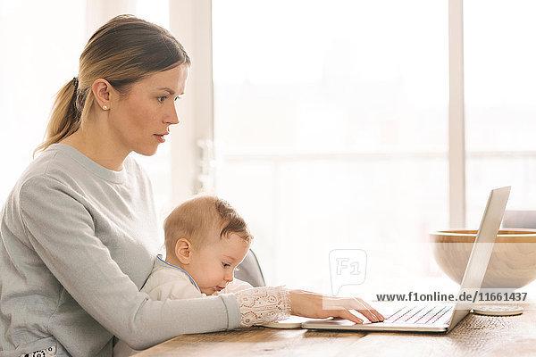 Mutter arbeitet und kümmert sich zu Hause um ihr Baby Mutter arbeitet und kümmert sich zu Hause um ihr Baby