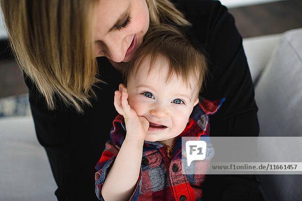 Porträt eines männlichen Kleinkindes  das auf dem Schoß der Mutter sitzt und am Daumen lutscht