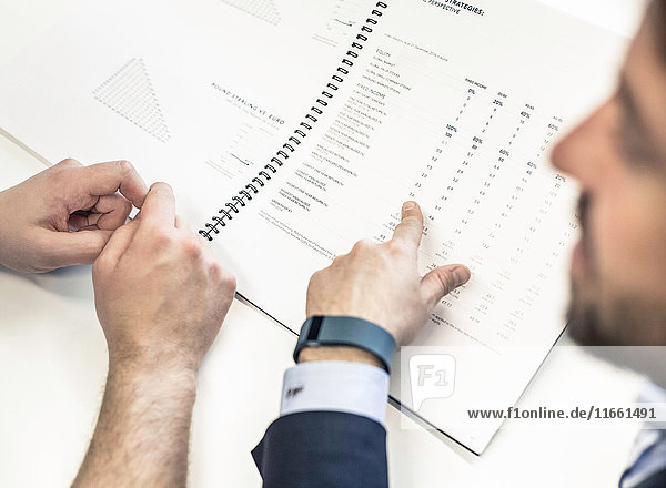 Over shoulder view of two businessmen at office desk pointing at paperwork