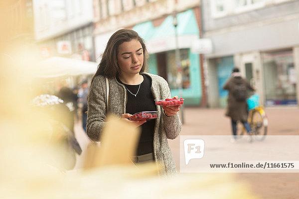 Junge Frau vergleicht Himbeerkörbchen am Marktstand
