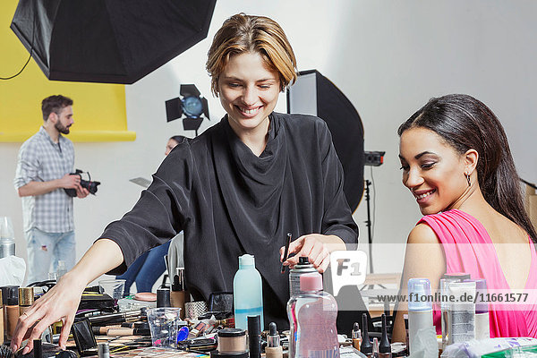Fashion model and make up artist getting ready in photography studio