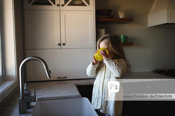 Mädchen an Küchenspüle Trinkwasser