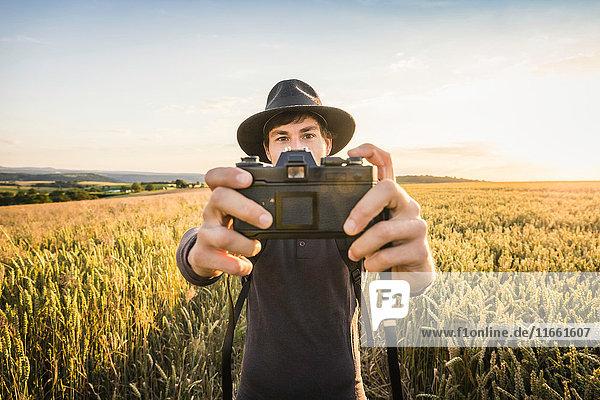 Mid adult man  standing in field  taking selfie with SLR camera  Neulingen  Baden-Württemberg  Germany