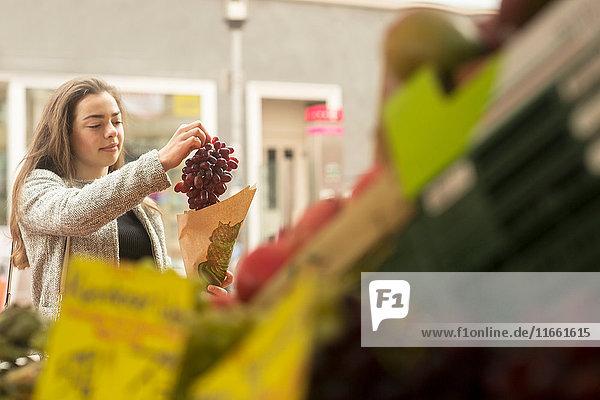 Junge Frau kauft Traube am Marktstand