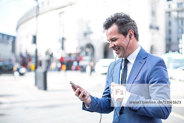 Geschäftsleute in der Straße mit Smartphone und Ohrhörern  London  UK