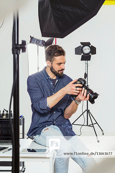 Male photographer reviewing photography shoot on digital SLR in photography studio