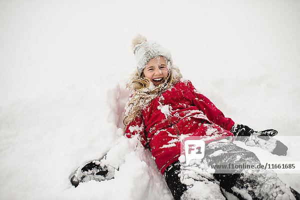 Smiling girl lying on back and covered in snow