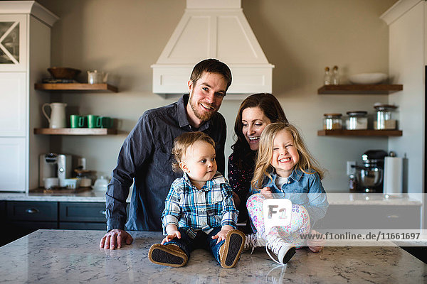 Portrait of mid adult parents with girl and baby boy on kitchen counter
