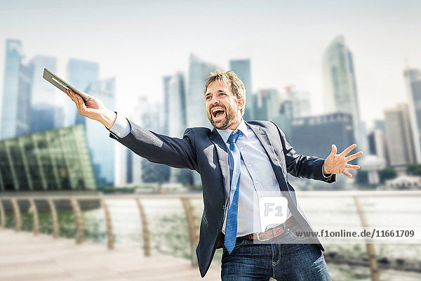 Happy businessman holding out digital tablet on city waterfront
