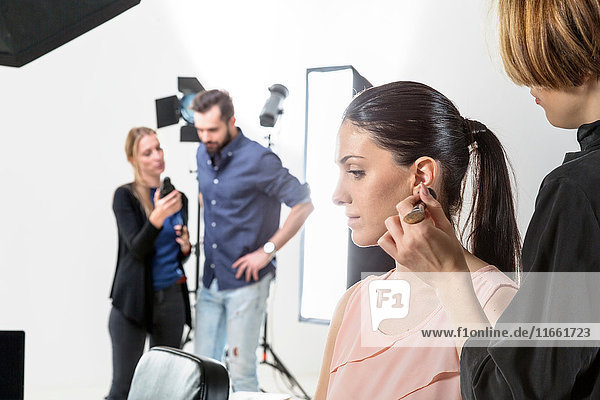 Make up artist applying blusher to fashion model in photography studio