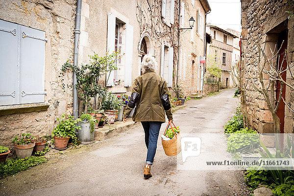 Rückansicht einer Frau  die in einer engen ländlichen Straße geht  Bruniquel  Frankreich