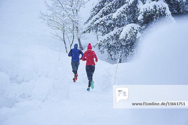 Rückansicht von Läuferinnen und Läufern  die im Tiefschnee auf der Bahn laufen  Gstaad  Schweiz