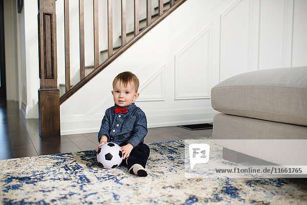 Portrait of male toddler in red bow tie sitting on floor with soccer ball