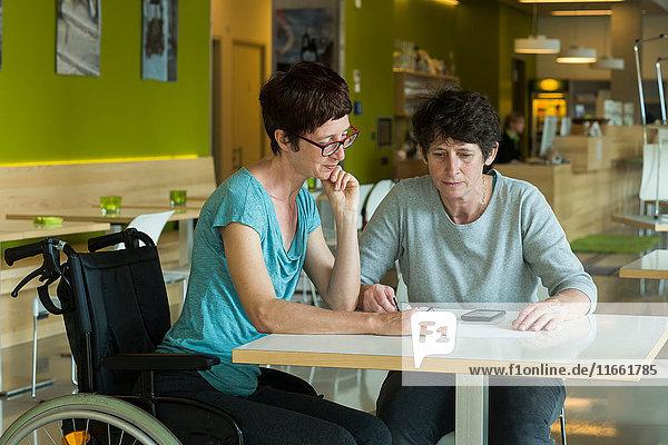 Frau im Rollstuhl  am Restauranttisch sitzend  im Gespräch mit Freund