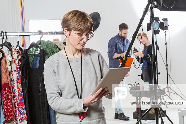 Stylist looking at digital tablet in photography studio