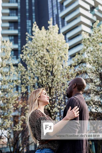 Junges Paar  das sich in der Stadt umarmt und anstarrt.