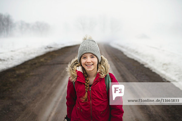 Portrait of girl in knit hat standing in middle of dirt road in fog