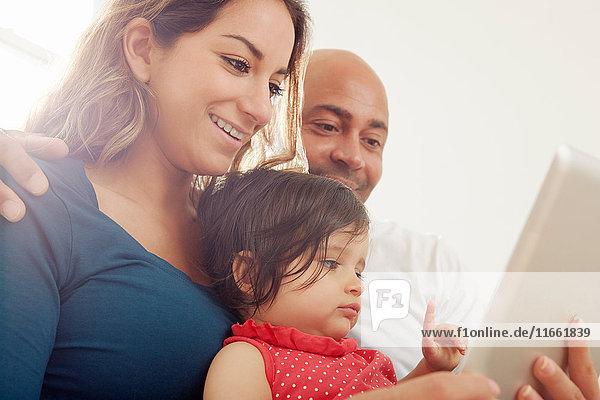 Kleines Mädchen sitzt auf dem Sofa  die Eltern schauen auf das digitale Tablet