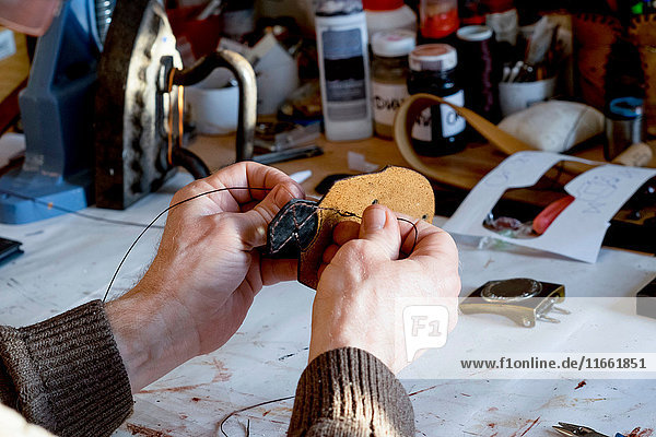 Man's hands stitching leather at workbench